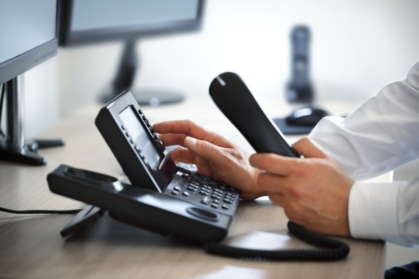 1-voip service review voip services man dialing number on voip phone in office