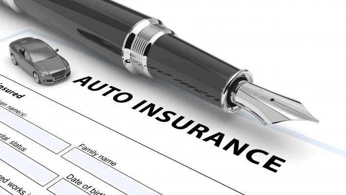 Picture of pen above auto insurance agreement.