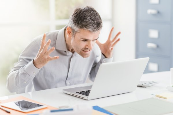 Advanced System Optimizer software system optimizer utility software overview benefits angry man frustrated annoyed in front of white laptop in office