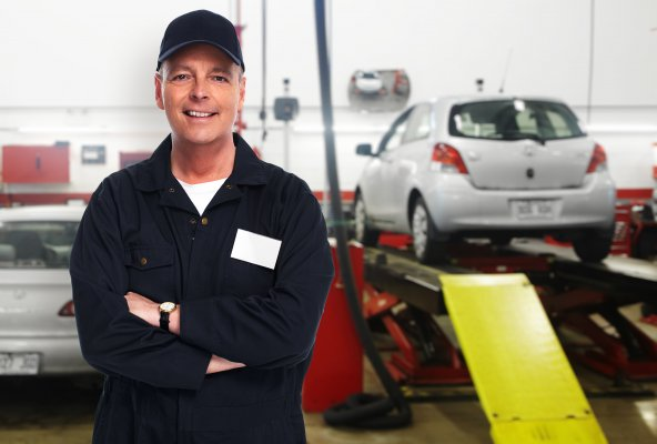 best extended car warranty services providers happy mechanic in uniform smiling towed car on platform in the background