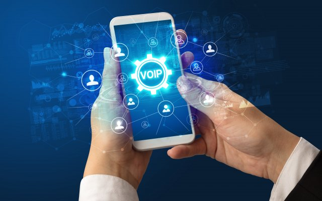 voip services best residential voip providers home voip 2020 man holding smartphone voip on display blue background