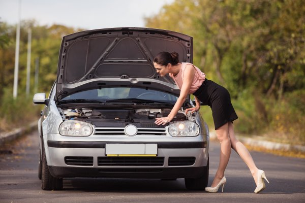 USAA MBI mechanical breakdown insurance woman checking car under the hood car on the road