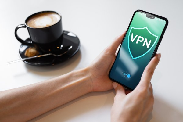 vpn on smartphone cup of coffee holding a smartphone vpn services