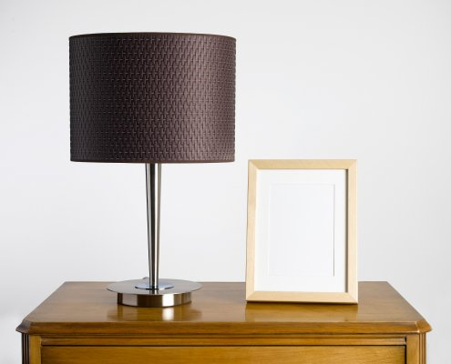 Digital picture frame on a desk by a lamp