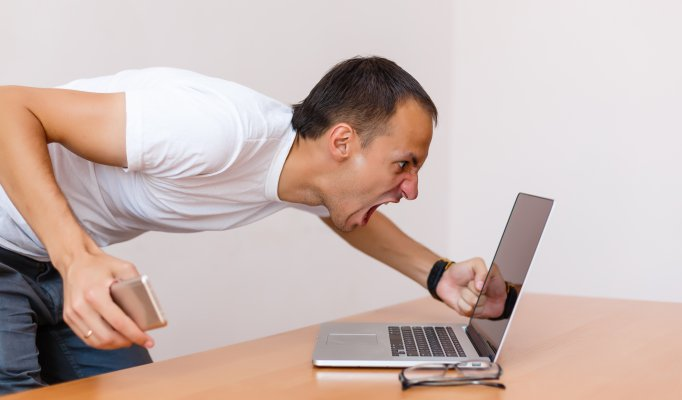 man screaming at laptop frustrated angry vpn services slow internet connection