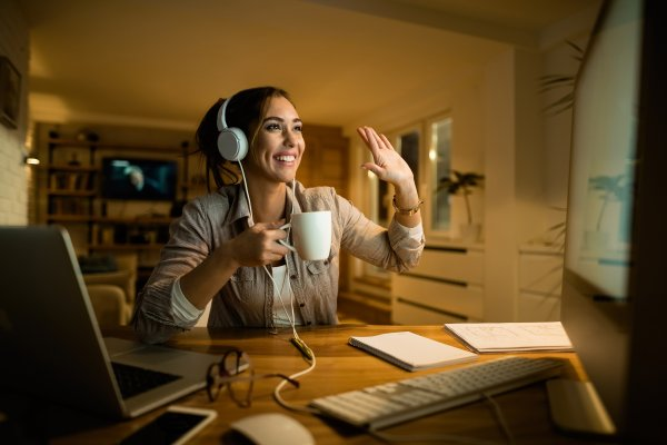 features vonage residential plans voip service woman video chat on computer with headphones and coffee mug in hand waving happy smiling