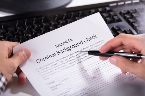 background check service truthfinder cost price completing request for criminal background check with pen on paper