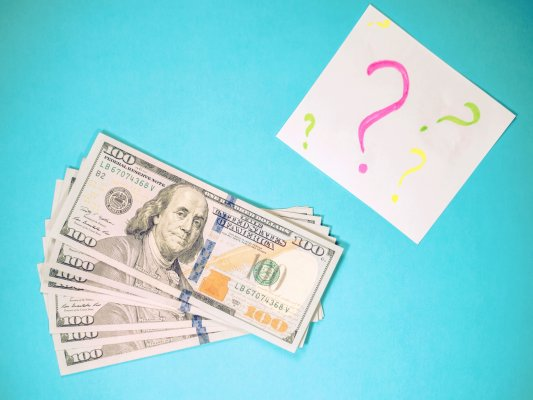 price cost pay background check service question marks on paper dollar bills blue background