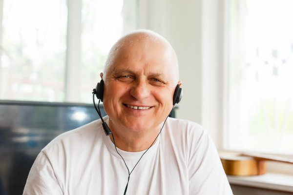 A man with a VOIP headset on, smiling a lot