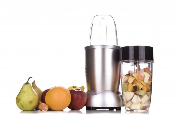 Small blender with fruit around it