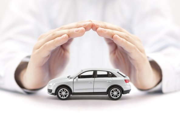 extended car warranty services hands holding protecting toy car