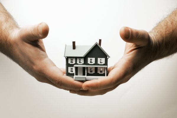 hands holding miniature house home design software