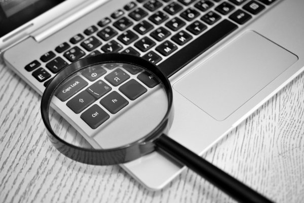us search online background check service review magnifying glass over laptop keyboard