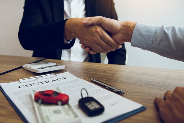 usaa extended car warranty service signing contract shaking hands contract red toy car and car keys on the table on the contract