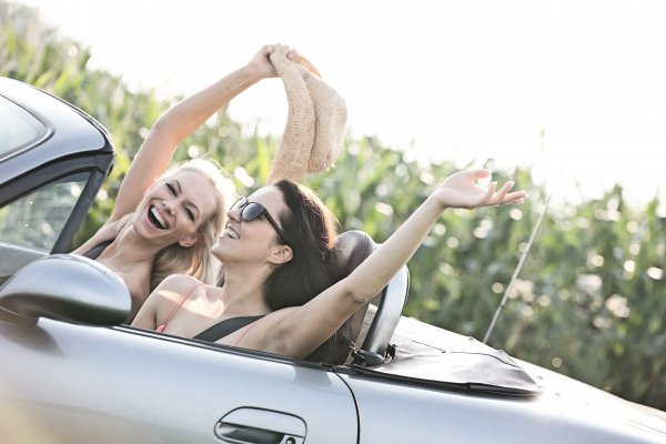 girls in convertible car smiling driving extended car warranty