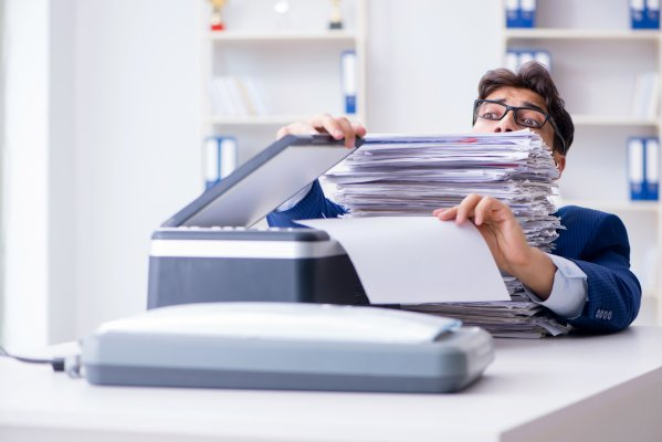 sfax online fax service features benefits man with glasses in office buried in files faxes fax machine