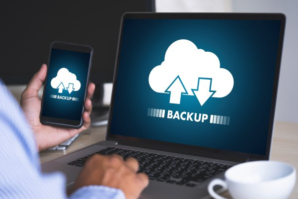 online backup cloud service spideroak one man backing up content on laptop holding smartphone white cup of coffee near laptop