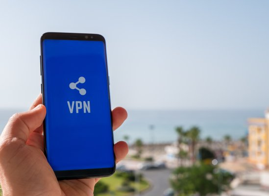 features turbo vpn smartphones mobile devices hand holding smartphone blue screen and vpn exterior beach