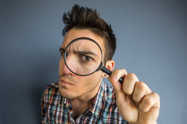 us search online background check service features man looking through magnifying glass