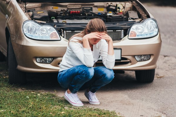 extended car warranty services woman upset next to broken car with open hood