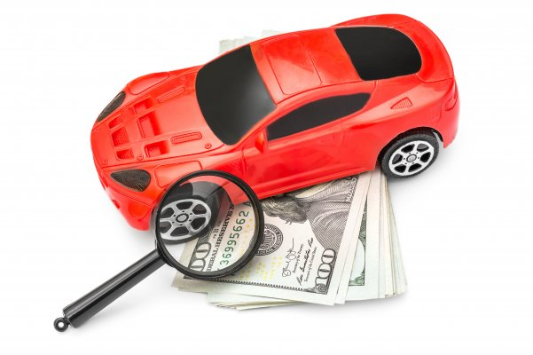 root car insurance price cost red car magnifying glass over dollar bills white background