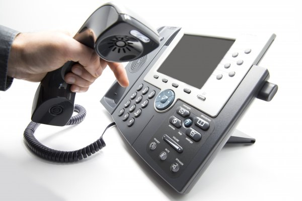 cost pricing axvoice voip service hand holding voip phone dialing making phone call